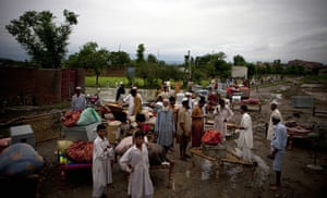 Pakistan floods: Pakistani villagers stand with their belongings rescued from houses