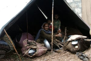 Pakistan floods: An elderly Pakistani woman sits with two children in a tent