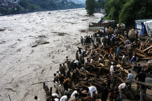 Pakistan floods: Pakistani residents watch the flood water in Muzaffarabad
