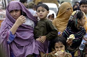 Pakistan floods: Pakistani women wait for transport from a flood hit village near Nowshera