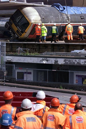 Potters Bar train crash: Railway workers watch removal of railway carriage from Potters Bar station