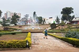 Kigali: Worker waters plants in Place de l'Unite Nationale in Kigali, Rwanda