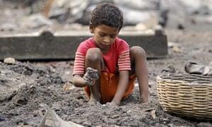 An Indian boy breaks coal at a waste dump near Kolkata