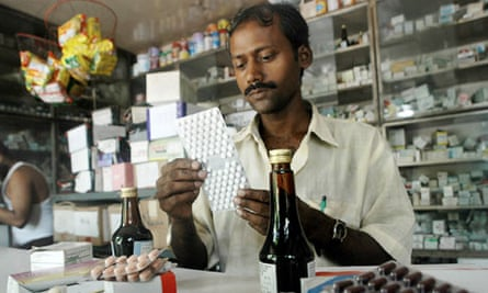 An Indian pharmacy assistant counts tablets