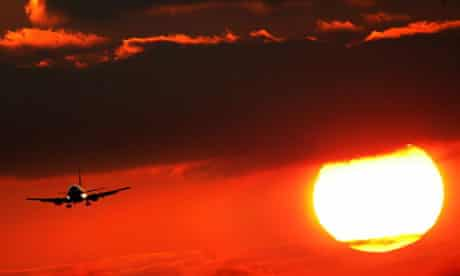 An aeroplane in front of the setting sun. Climate change global warming