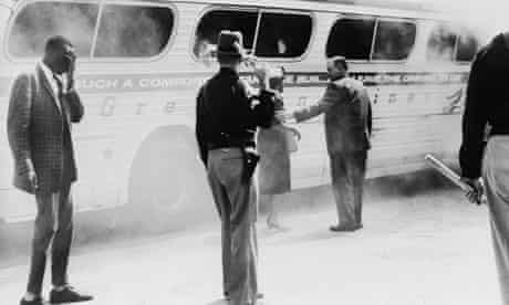 Patrolmen guard a burning Greyhound bus after a mob of white supremacists attacked it in 1961
