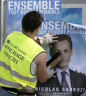 Bettencourt case 2: An employee sticks posters of presidential candidate Nicolas Sarkozy