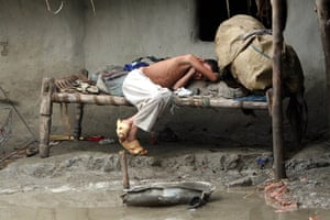 Pakistan floods: An exhausted boy has a nap in his flooded house in Peshawar