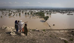 Pakistan floods: A person points towards their flooded home from a hilltop at Nowshera