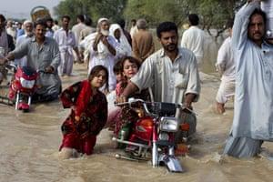 Pakistan floods: A man evacuates his children through waist-deep waters in Nowshera