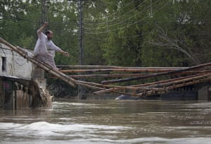 Pakistan floods: A man crosses a makeshift bridge to escape his flooded home in Nowshera