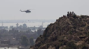 Pakistan floods: Residents watch from a nearby hill as army helicopters fly past