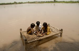 Pakistan floods: Children sit on a bed to eat their food in a flood-hit area of Qasim Bella