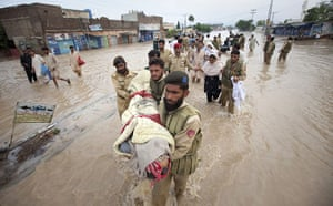 Pakistan floods: Army soldiers carry the body of a dead man to higher ground