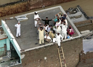 Pakistan floods: Stranded villagers wait for helicopters on the roof of a house in Nowshera