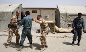British soldiers train an Afghan police officer at the British army base Task Force Helmand