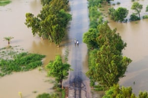 aerial update: Flood victims wade through flood waters to get to higher ground
