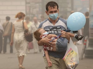 Moscow smog: A man carries a child wearing medical masks to protect from smog in Moscow