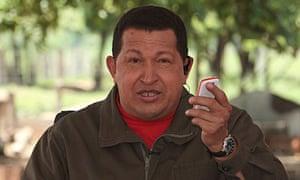Hugo Chavez holds a mobile phone
