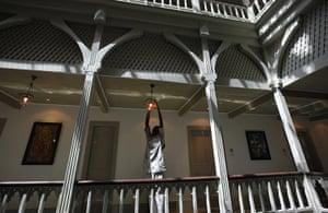 Taj Mahal Palace hotel: An employee of the Taj Palace Hotel checks a light fitting