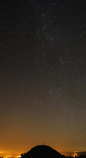 Perseid meteors: A meteor streaks past stars in the night sky over Leeberg hill