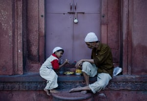 Ramadan Update: An Indian Muslim man and child break their fast on the first day of Ramadan