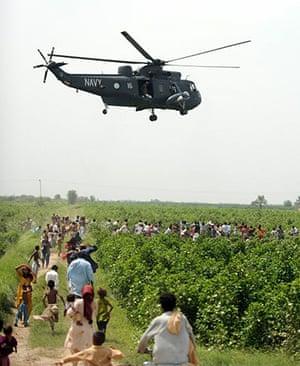 Pakistan Flood Disaster: Pakistani flood survivors rush towards a helicopter distributing aid