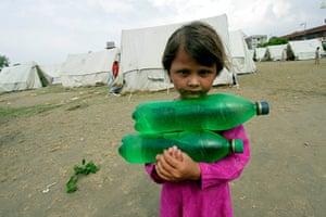 Pakistan Flood Disaster: A flood affected girl carries bottles of drinking water, Pakistan