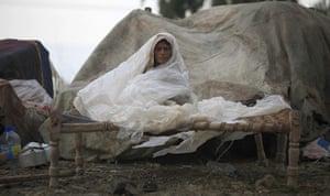 Pakistan flood survivors: A long-term Afghan refugee shields herself from rain