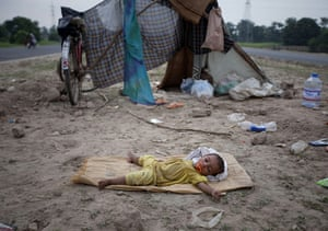 Pakistan flood survivors: A young flood victim sleeps next to a road after her family evacuated