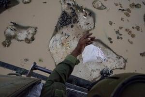 Pakistan flood survivors: A Pakistani Army crewman drops relief supplies to flood victims