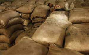 Pakistan flood survivors: A World Food Program (WFP) worker sleeps on top of flour sacks