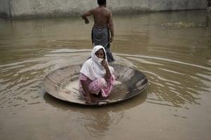Pakistan flood survivors: A flood survivor tows his mother to a safer area in Khangarh