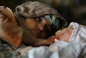 Pakistan flood survivors: A Pakistani woman looks at her day old baby at a camp