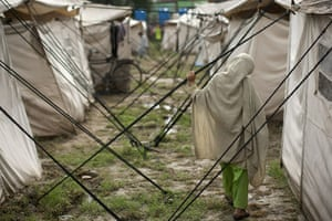 Pakistan flood survivors: A flood-affected girl walks outside her tent in the compound of a college