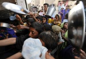 Pakistan flood survivors: Pakistani flood survivors struggle for charity food near a camp in Sukkur