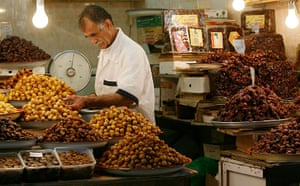 Pakistan flood survivors: A vendor selling dates works at his stall at a market in Kuwait City
