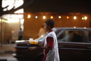 Ramadan: A volunteer youth offers passersby free drinks in a Cairo street, Egypt
