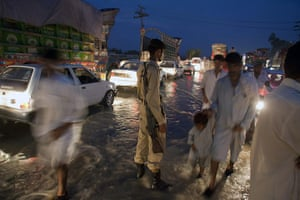 pakistan flooding: A paramilitary soldier stands to control the traffic