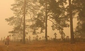 Forest fires in Russia: A woman walks in dense smoke near a cemetery in the village of Beloomut