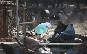 Forest fires in Russia: A woman inspects the remains of her burnt house at the edge of Voronezh