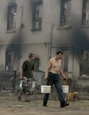 Forest fires in Russia: People carry water past a house destroyed by fire in Mokhovoye