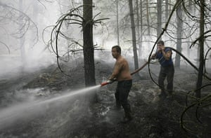 Forest fires in Russia: A firefighter douses flames in trees in the village of Lesnoye