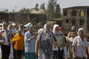Forest fires in Russia: People carry icons during a religious procession in front of burnt houses