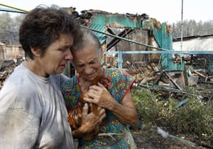 Forest fires in Russia: Women react while standing in front of the ruins of a house in Voronezh
