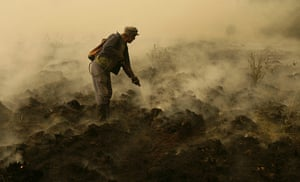 Forest fires in Russia: A firefighter work to extinguish a peat fire in a forest near Ryazanovka