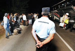 Roma deportation: French policemen stand guard next to a bus