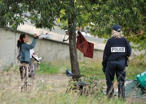 Roma deportation: A woman belonging to the Roma community takes shoes from a clothes line