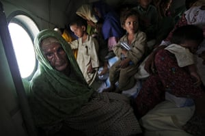 Pakistan Flood Update: Pakistanis displaced by flooding sit in a Pakistan Army helicopter