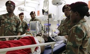 Soldiers attend to a patient at the Chris Hani-Baragwanath hospital in Soweto